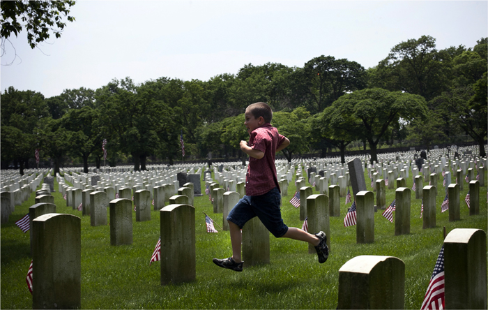 Matthew Kinneary runs past gravestones during a visit to Cyprus Hills National Cemetery