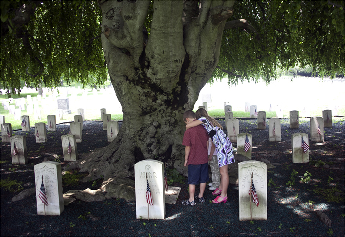 Matthew and Kelly Kinneary look at a gravestone during a visit to Cyprus Hills National Cemetery