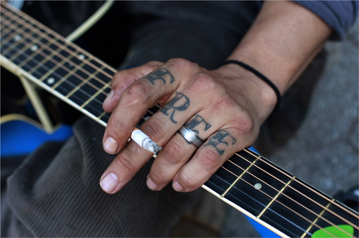 Occupy Wall Street activist with the word &quot;Free&quot; tattooed on his hand plays a guitar during a May Day demonstration in New York