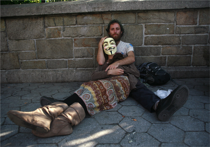 Occupy Wall Street activists rest on a sidewalk during a May Day demonstration in New York