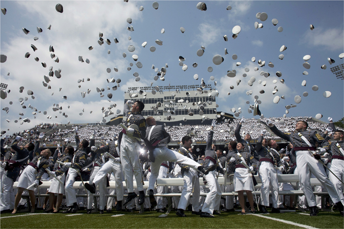 U.S. military academy cadets throw their caps into the air after their graduation ceremony at West Point