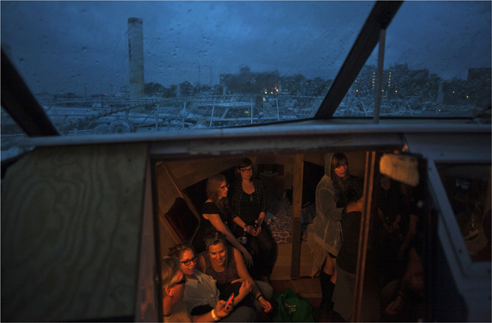 Guests get together for drinks in the cabin of a boat during a downpour at the Boatel in New York